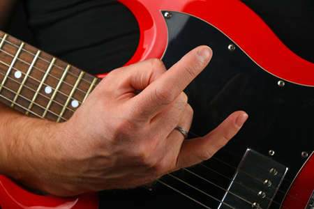 sg: Male hand holding red sg guitar body under neck with devil horns rock metal sign isolated on black background Stock Photo