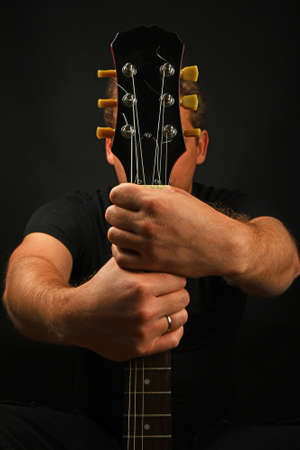 sg: Man sitting and holding guitar neck with two hands isolated on black background