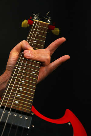 sg: Male hand holding red sg guitar neck with devil horns rock metal sign isolated on black background Stock Photo