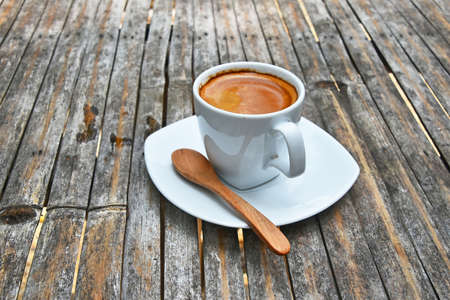 crema: One white cup full of espresso coffee with brown crema on porcelain saucer with wooden spoon on old vintage bamboo table