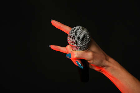 devil horns: Woman hand with microphone with devil horns rock metal sign highlighted with red gun projector isolated on black background
