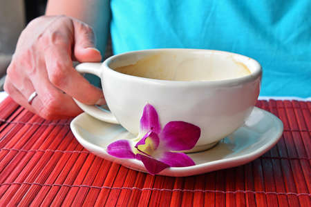 porcelain flower: Woman hand holding half empty latte coffee cup with orchid flower at porcelain saucer