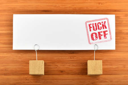 fuck: Fuck off red rude stamp on one big white paper note with two wooden holders on wooden bamboo background for presentation