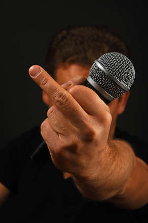 insult: Male hand holding microphone with finger fuck off insult ignore gesture with head behind on black background