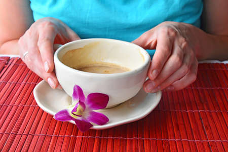 porcelain flower: Woman two hands holding half empty latte coffee cup with orchid flower at porcelain saucer Stock Photo