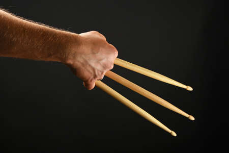wolverine: Famous wolverine claws heroic gesture, man hand holding three wooden drumsticks over black background, back view, horizontal Stock Photo