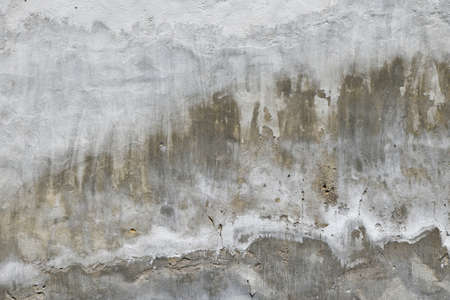 defects: Old white and grey painted lime plaster concrete wall with weatherstains, runs and defects Stock Photo