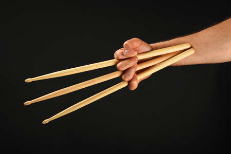 wolverine: Famous wolverine claws heroic gesture, man hand holding three wooden drumsticks over black background, front view, horizontal