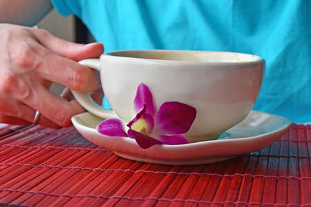 porcelain flower: Woman hand holding latte coffee cup with orchid flower at porcelain saucer