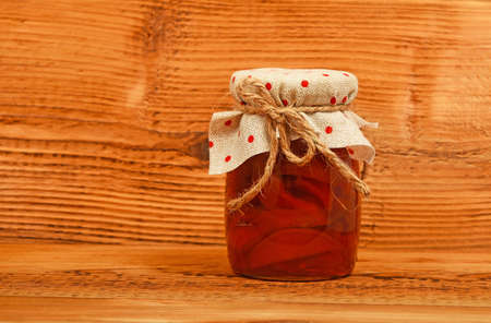 unpainted: One glass jar of homemade quince jam with textile top decoration at unpainted brown vintage wood