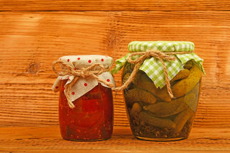 salad decoration: One glass jar of homemade pickled cucumbers with green checkered textile top decoration and eggplant salad at unpainted vintage wooden surface