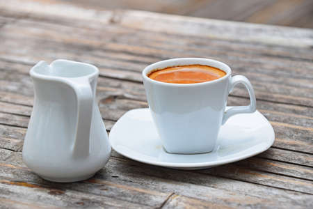 crema: One white cup full of espresso coffee with brown crema on porcelain saucer with small milk jug on old vintage bamboo wooden table