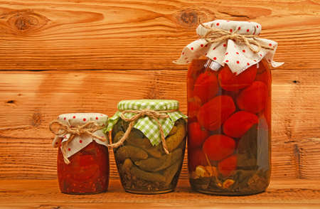 salad decoration: Three glass jars of homemade conserves, eggplant pepper salad, pickled tomatoes and cucumbers with textile decoration over brown unpainted wood