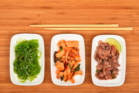 seaweeds: Three portions of seafood marinated salad with octopus cuttlefish, squid and seaweeds in small white plates with chopsticks on bamboo wood, top view Stock Photo