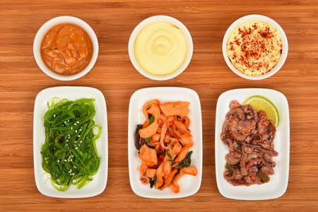 calamares: Tres porciones de pescados y mariscos marinados con ensalada de pulpo de sepia, calamar y algas marinas en pequeñas placas blancas con la salsa en la mesa de madera, vista desde arriba Foto de archivo