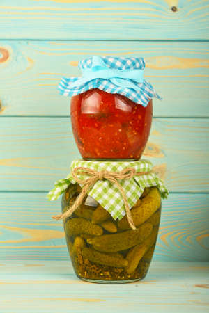 salad decoration: One glass jar of homemade eggplant pepper salad on jar of pickled cucumbers with green checkered textile decoration over blue painted wooden surface