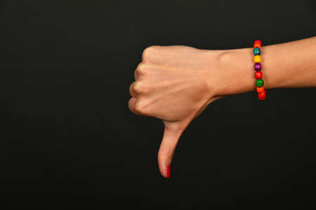 not painted: Woman hand with red nails and colorful wooden painted beads bracelet shows not ok thumb down dislike gesture sign over black background