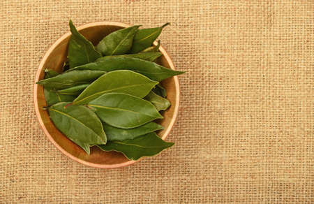 Wooden bowl of green bay laurel leaves on brown burlap jute canvas background