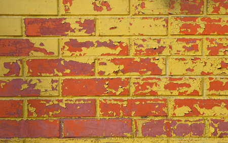 defects: Old grunge red brick wall painted with yellow paint with flakes, stains and defects