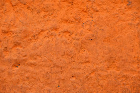 defects: Orange painted old dirty concrete plaster wall with paint racks, defects and stains