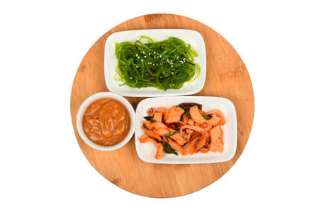 seaweeds: Two portions of seafood marinated salad with octopus cuttlefish and seaweeds in with sauce on round wooden board, top view Stock Photo