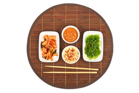 seaweeds: Two portions of seafood marinated salad with octopus cuttlefish and seaweeds in with chopsticks and sauce on dark round bamboo mat, top view