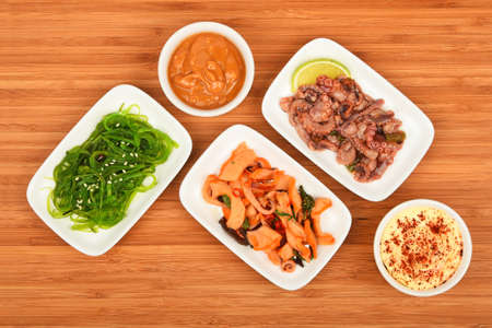 seaweeds: Three portions of seafood marinated salad with octopus cuttlefish, squid and seaweeds in small white plates with sauce on wooden table, top view Stock Photo