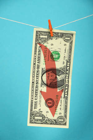 stagnation: Stagnation and volatility of American economy and US dollar, one dollar banknote with red arrow down hanged with pin at rope over blue Stock Photo