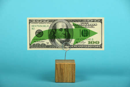 stagnation: Stagnation and support of American economy and US dollar, one dollar banknote with green horizontal arrow on holder over blue background Stock Photo