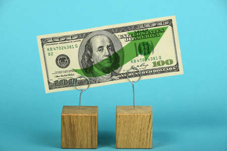 two us dollar: Growth and support of American economy and US dollar, one dollar banknote with green arrow up on two holders over blue background