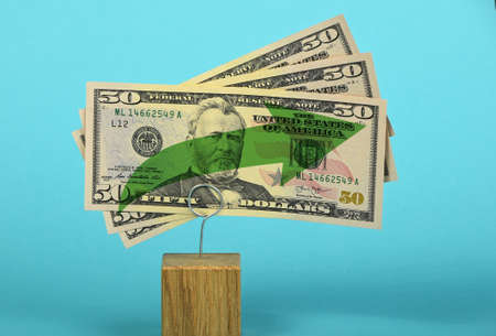two us dollar: Growth and support of American economy and US dollar, tree fifty dollars banknote with green arrow up on two holders over blue background