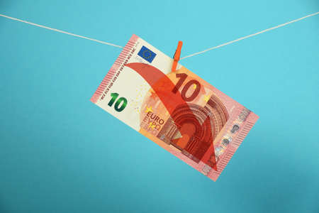 economy crisis: European economy crisis, decline of Euro, ten Euro banknote with red arrow down hanged descending with pin at rope over blue background Stock Photo