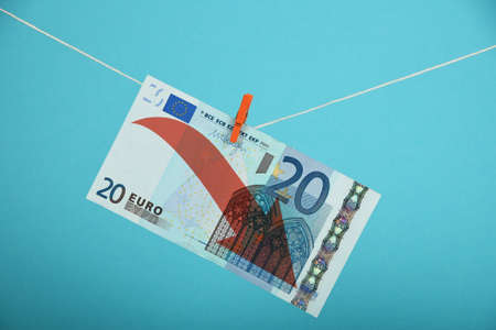 twenty euro banknote: European economy crisis, decline of Euro, twenty Euro banknote with red arrow down hanged descending with pin at rope over blue background Stock Photo