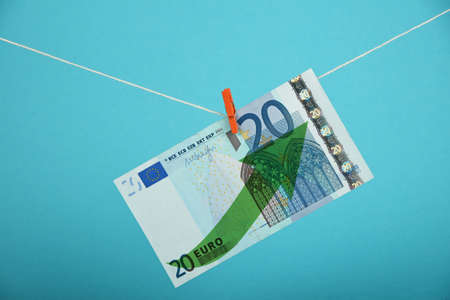 twenty euro banknote: European economy growth, strengthening of Euro currency, twenty Euro banknote with green arrow up hanged ascending with pin at rope over blue