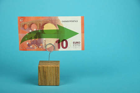 stagnation: Stagnation and support of European economy and Euro currency, ten Euro banknote with green horizontal arrow on holder over blue background