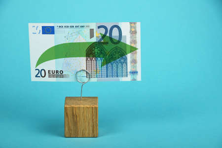 twenty euro banknote: Stagnation and support of European economy and Euro currency, twenty Euro banknote with green horizontal arrow on holder over blue background Stock Photo