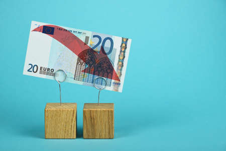 economy crisis: European economy crisis, decline of Euro currency, twenty Euro banknote with red arrow down at wooden metal holders over blue background