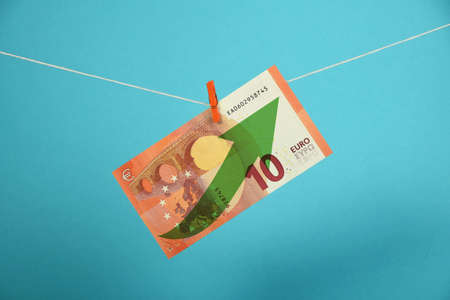 strengthening: European economy growth, strengthening of Euro currency, ten Euro banknote with green arrow up hanged ascending with pin at rope over blue Stock Photo