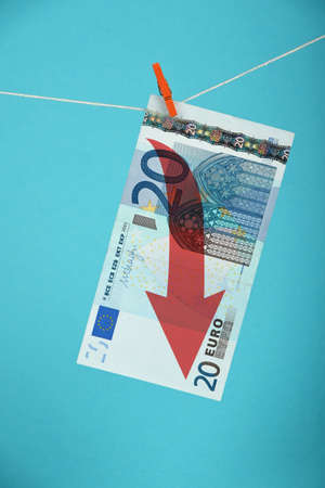 twenty euro banknote: European economy crisis, decline of Euro currency, twenty Euro banknote with red arrow down hanged descending with pin at rope over blue background