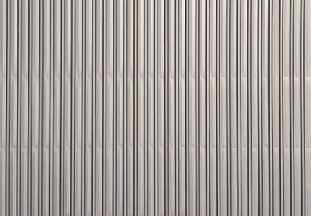 channeled: Unpainted aluminum grey corrugated goffered metal wall texture