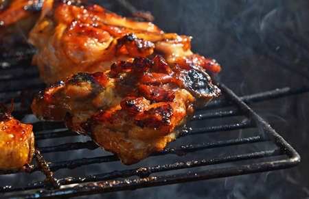chargrill: Grilled barbecue chicken legs meat portions cooked on fire grill close up