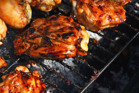 portions: Grilled barbecue chicken legs meat portions cooked on fire grill close up