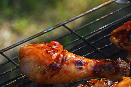 chargrill: Grilled barbeque chicken legs meat portions cooked on fire grill close up