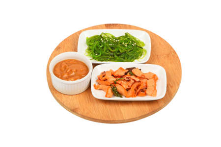 seaweeds: Two portions of seafood marinated salad with octopus cuttlefish and seaweeds in with sauce on round wooden board