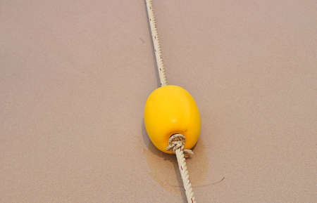 beach buoy: Yellow polystyrene sea marker buoy with cable tow on wet sand sea beach Stock Photo