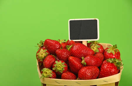 mellow: Mellow fresh red summer strawberries in wooden wicker basket with chalk blackboard price tag sign over green paper background, high angle view