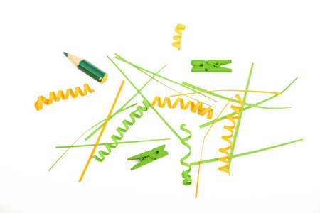 trumpery: Mixed colorful green and yellow paper pieces, clips, pencils and wooden painted clothespins isolated on white background Stock Photo
