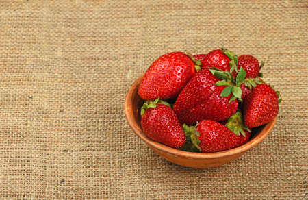 mellow: Mellow fresh red summer strawberries in rustic ceramic bowl on jute burlap canvas background, high angle view Stock Photo