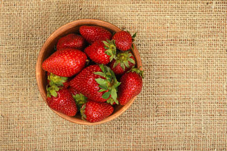 mellow: Mellow fresh red summer strawberries in rustic ceramic bowl on jute burlap canvas background, top view Stock Photo
