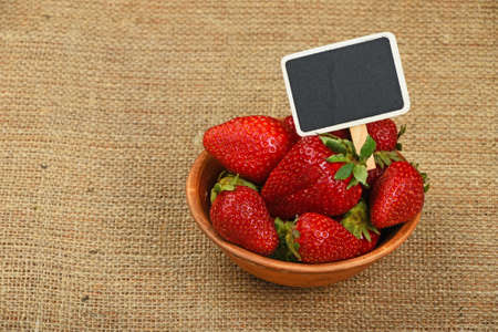 mellow: Fresh mellow red strawberries in rustic ceramic bowl with chalk blackboard price tag sign on jute burlap canvas background, high angle view Stock Photo